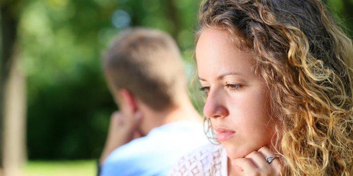 triste jeune couple assis sur le banc au parc