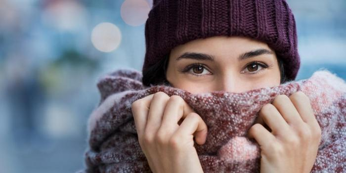 winter portrait of young beautiful woman covering face with woolen scarf closeup of happy girl feeling cold outdoor in th...